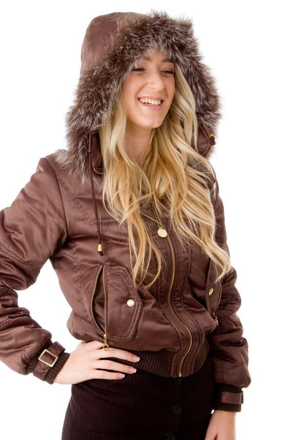 Side pose of smiling female wearing hood coat