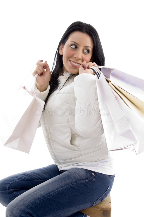 Side pose of smiling woman holding shopping bags royalty free stock images