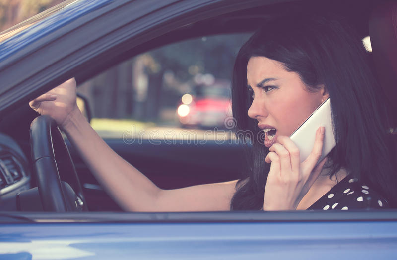 Side profile angry driver woman talking on mobile phone. royalty free stock images