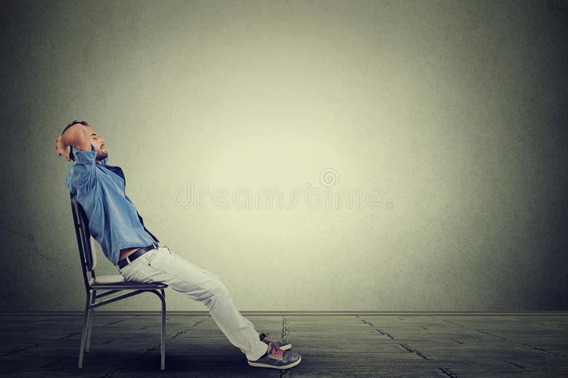 Side profile business man relaxes in his empty office stock image