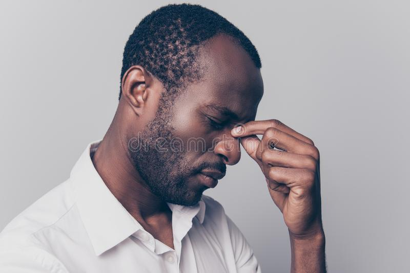 Side profile close up view portrait of nervous stressed depressed unsatisfied hard-working african man with closed eyes touching royalty free stock images