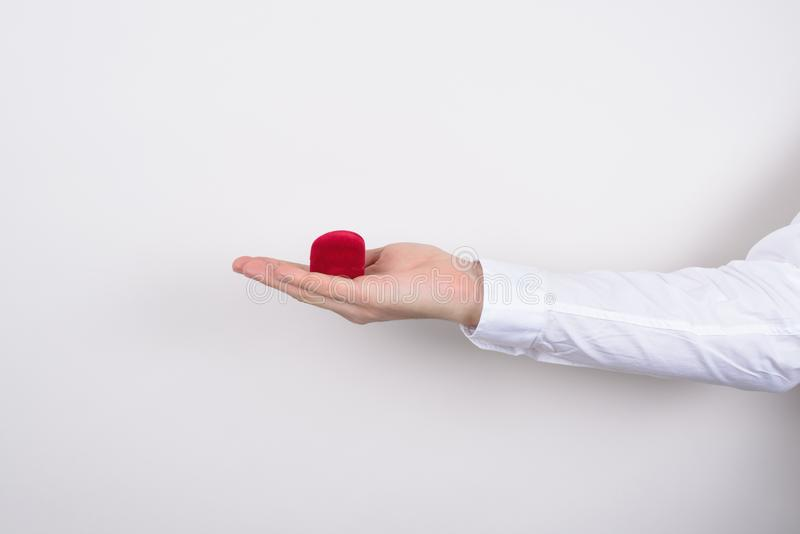 Side profile closeup cropped photo of hand holding closed red heart shaped small little box with ring inside isolated grey stock images
