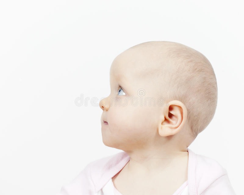 Side profile of a cute baby girl. Studio portrait side profile of a cute cherubic baby girl looking upwards with trusting eyes isolated on white royalty free stock photography