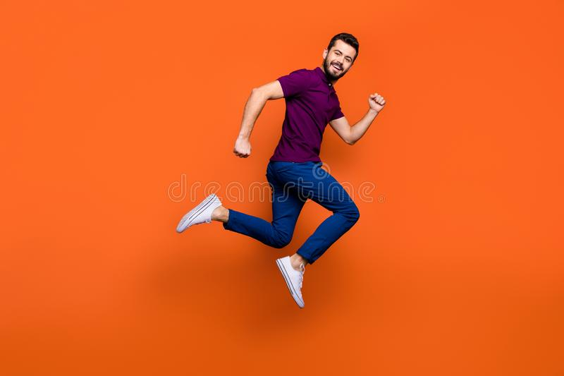 Side profile full length body size photo of crazy cheerful jumping running man in white sneakers aspiring to come for. Side profile full length body size photo royalty free stock photography