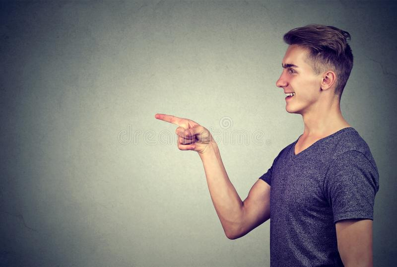 Side profile of a laughing young man pointing finger at someone. On gray wall background royalty free stock photos