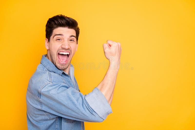 Side profile photo of cheerful positive crazy guy expressing rude scream on face showing muscles in jeans denim isolated royalty free stock images