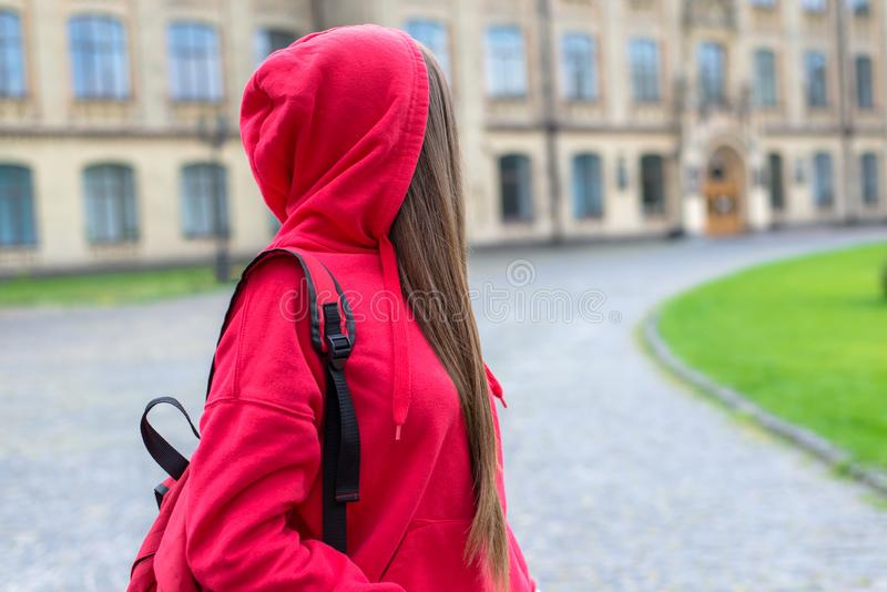 Side profile photo of sad unhappy sad regretful teen teenager hipster person looking back at university building.  royalty free stock images