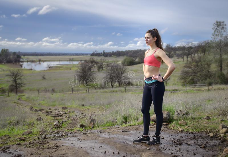 Side profile of pretty, woman jogger outdoors royalty free stock photo