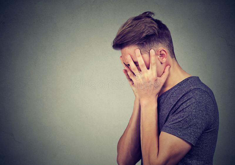 Side profile of a sad young man with hands on face looking down. Depression and anxiety disorder stock photos