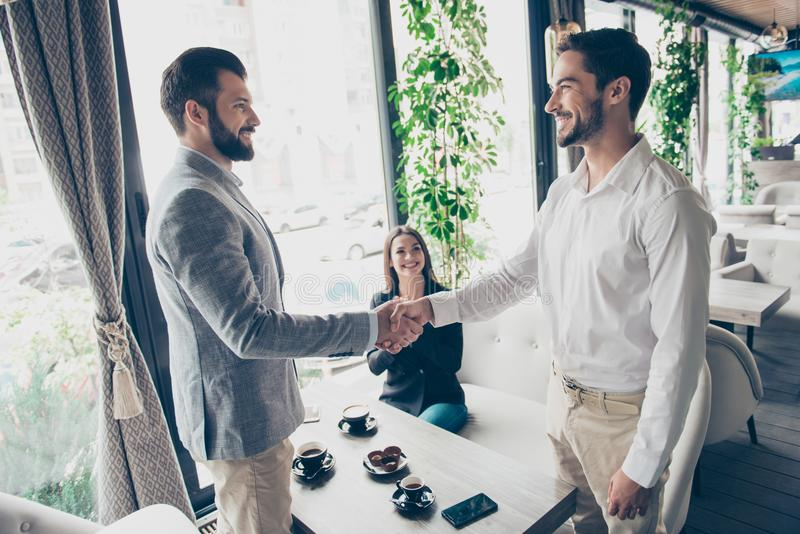 Side profile shot of two business partners in formal outfits making a deal about their business, shaking hands to complete the de. Al, lady is happy, sitting stock photography