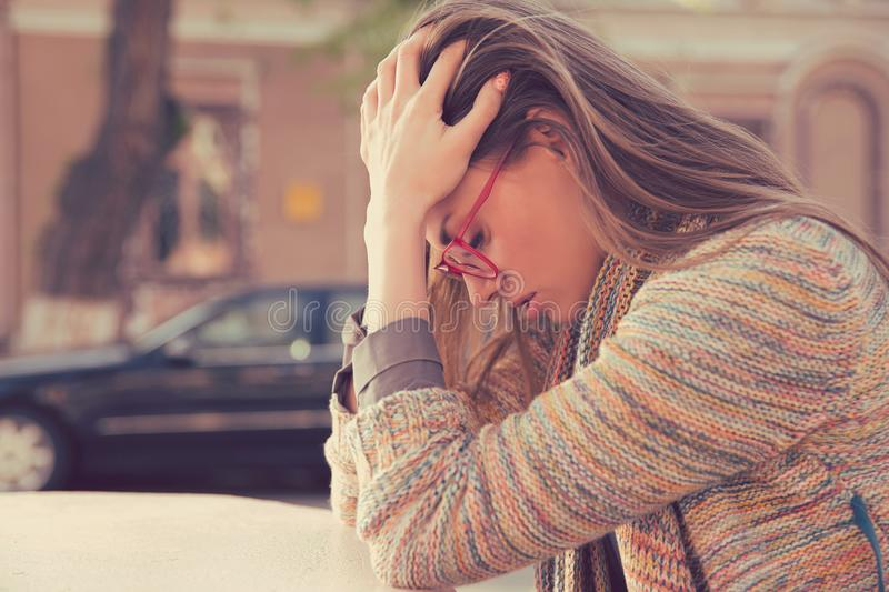 Side profile stressed sad young woman sitting outdoors stock image