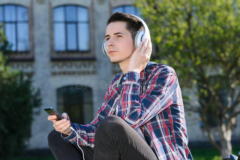 Side profile turned photo of concentrated guy enjoying cool clear sound from his new headset sitting on grass stock images