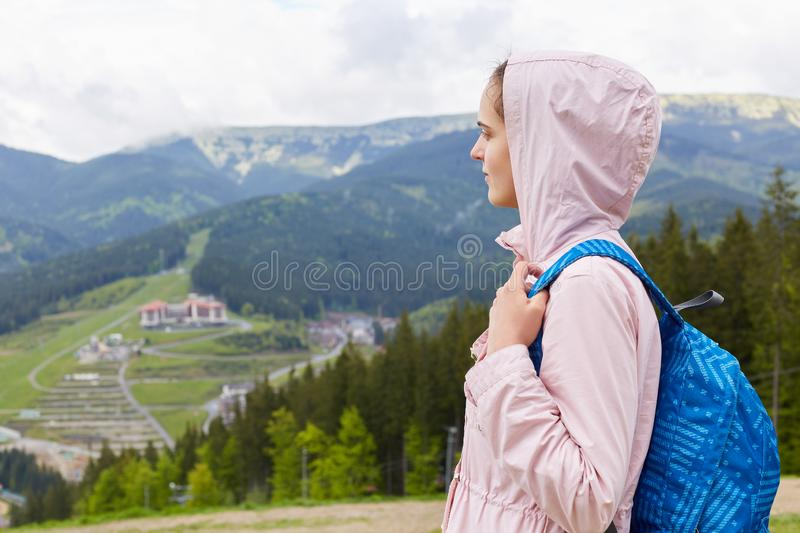 Side profile view of attractive beautiful girl, wearing casual rose jacket and blue rucksack, female backpacking and wandering. stock images