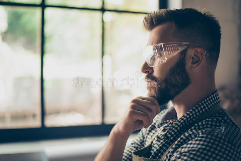 Side profile view portrait of bearded serious pensive concentrated confident builder wearing protective glasses, he is touching h royalty free stock images