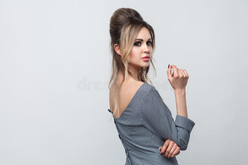 Side profile view portrait of beautiful attractive fashion model in grey dress with makeup and hairstyle standing, posing and royalty free stock photos