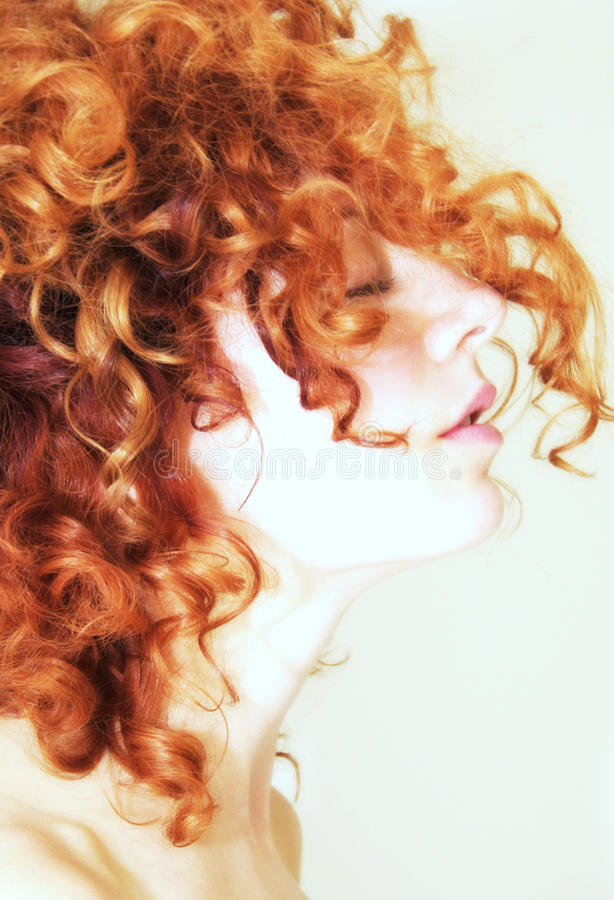 Side profile of woman with curly red hair royalty free stock image