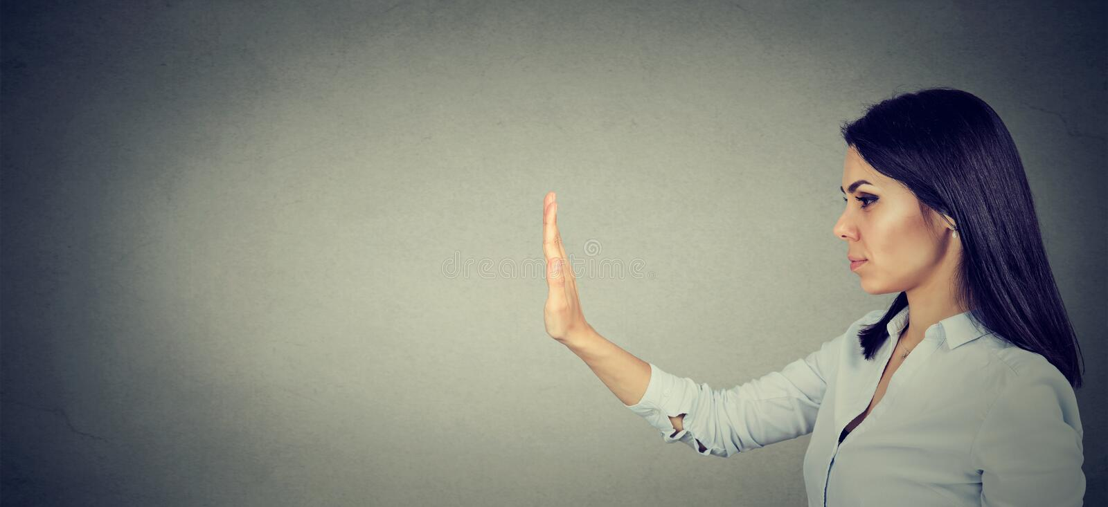 Side profile of woman with stop hand gesture. Side profile of young woman with stop hand gesture royalty free stock photo