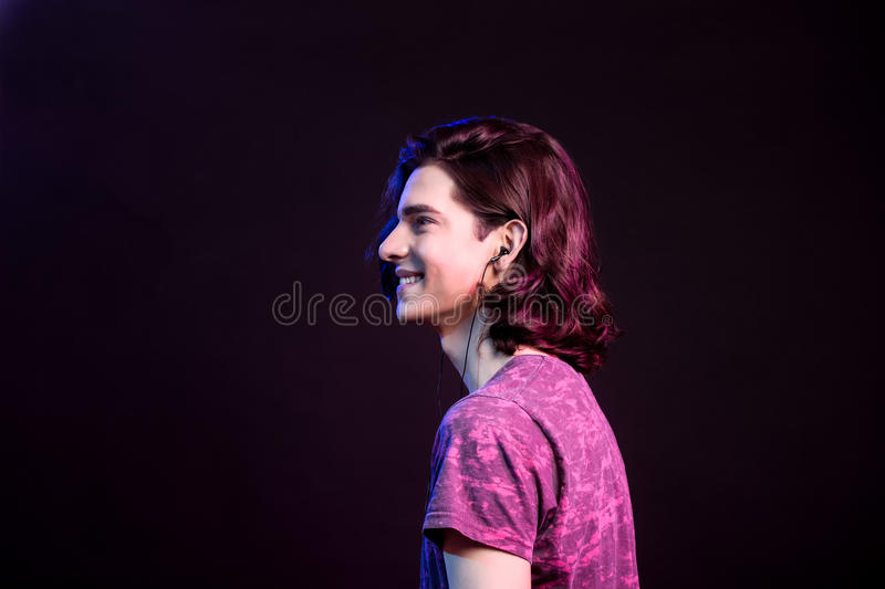 Side profile young man listening to sounds from earbuds. stock images