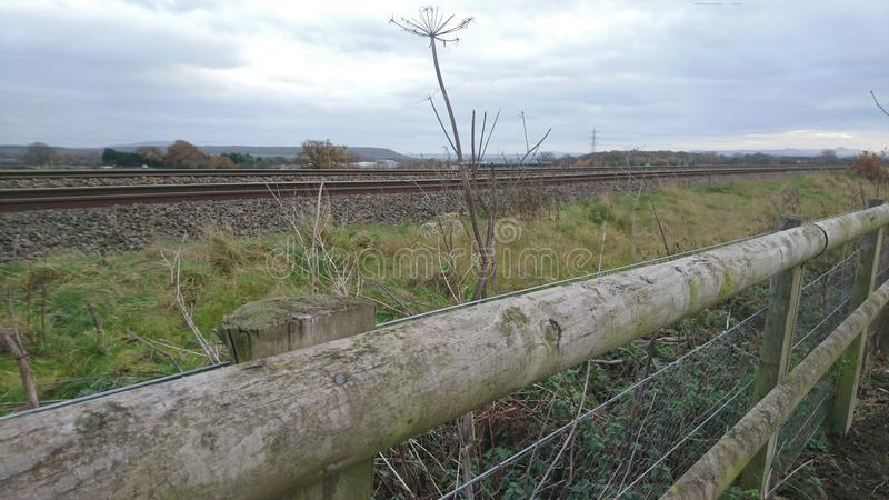 By the side of the railway tracks. Fence train track countryside vegetation overgrown travel waiting watching sidings cow parsley wooden steel looking down along stock image