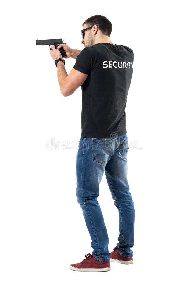 Side rear view of security guard pointing and aiming gun away stock photos