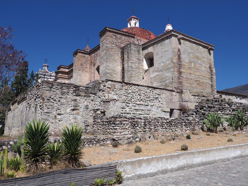 Side of San Pedro church in Mitla city, cobble road at archeological site of Zapotec culture on Oaxaca landscape, Mexico. Side of San Pedro church in Mitla city royalty free stock image