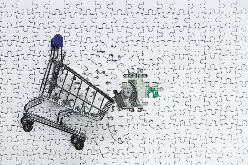 Side Shopping cart full of jigsaw puzzle on money dollar background, Business solution concept ,key for success stock image