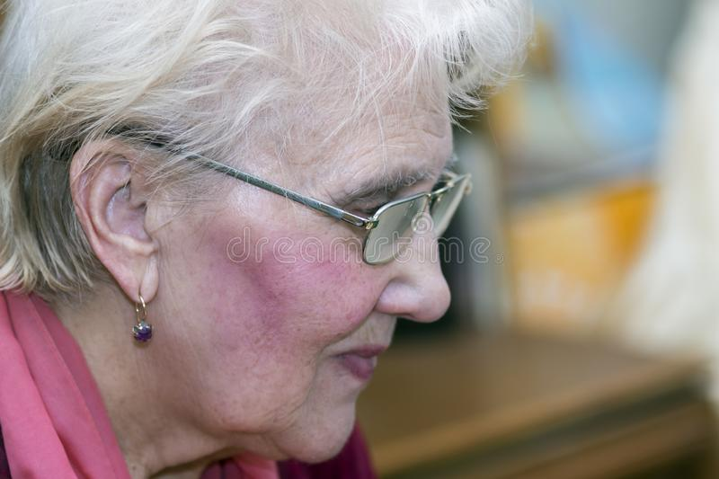 Aged woman in glasses with short gray hair stock photos