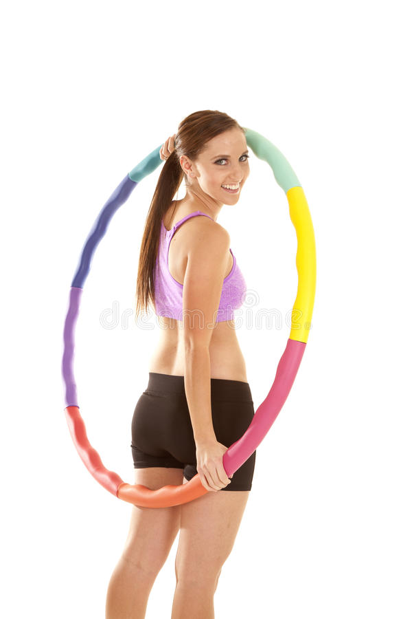 Side smile hoop. A woman holding on to her weighted hoola hoop with a smile on her lips stock image