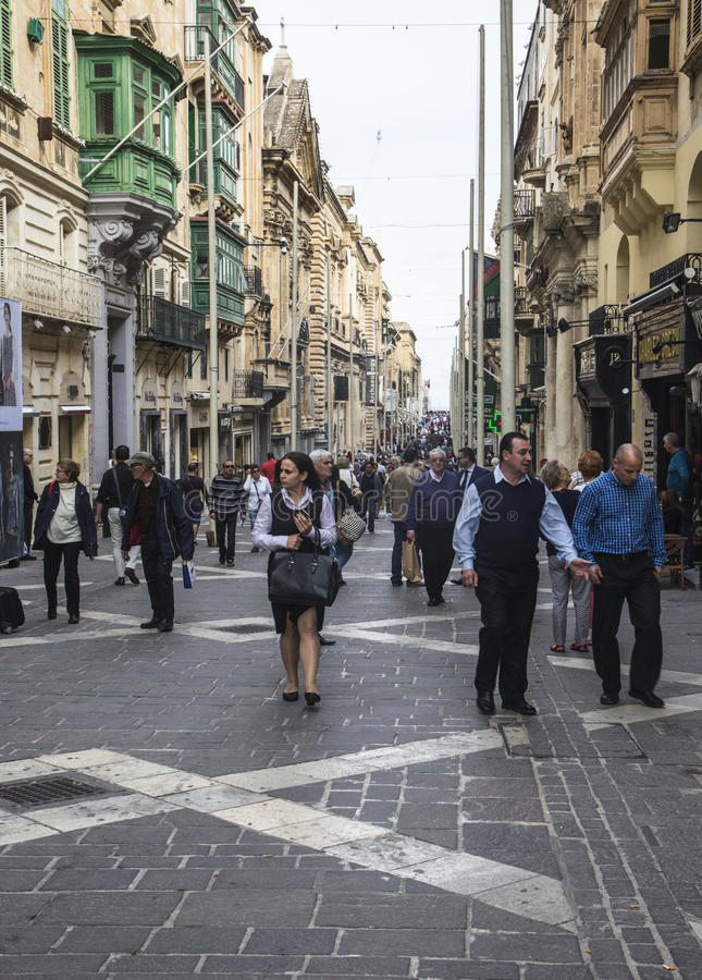 Side street in Malta`s capital city of Valletta on Malta. City workers and tourists in side street in Malta`s capital city of Valletta on Malta royalty free stock photos