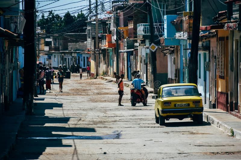 The side streets of Trinidad, Cuba. The busy side streets with yellow Lada parked in Trinidad, Cuba stock photo