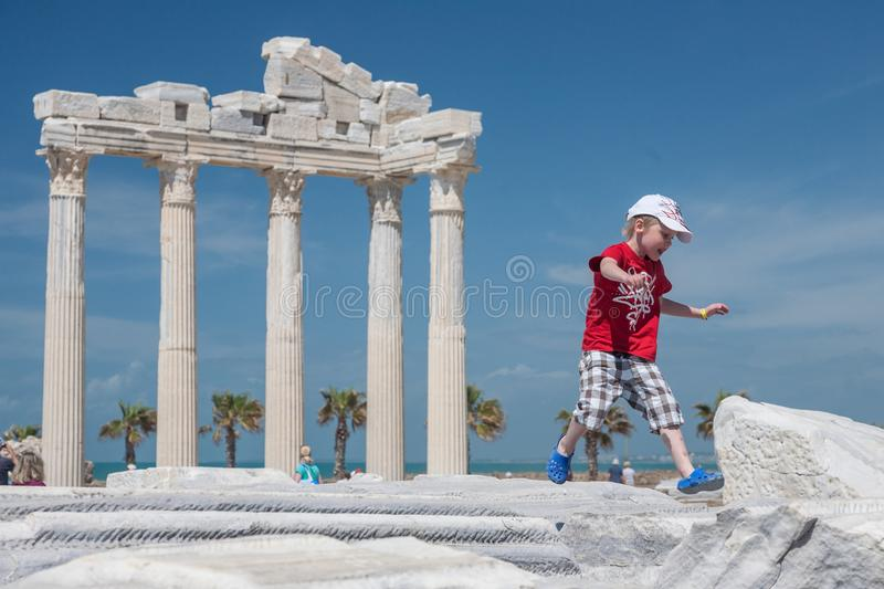 Small child jumps over the ancient roman ruins in front of the r royalty free stock photography