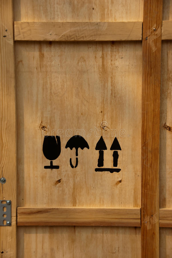 This Side Up Storage Crate. Wooden storage crate detail showing fragile, this side up, and moisture sensitive symbols royalty free stock photo