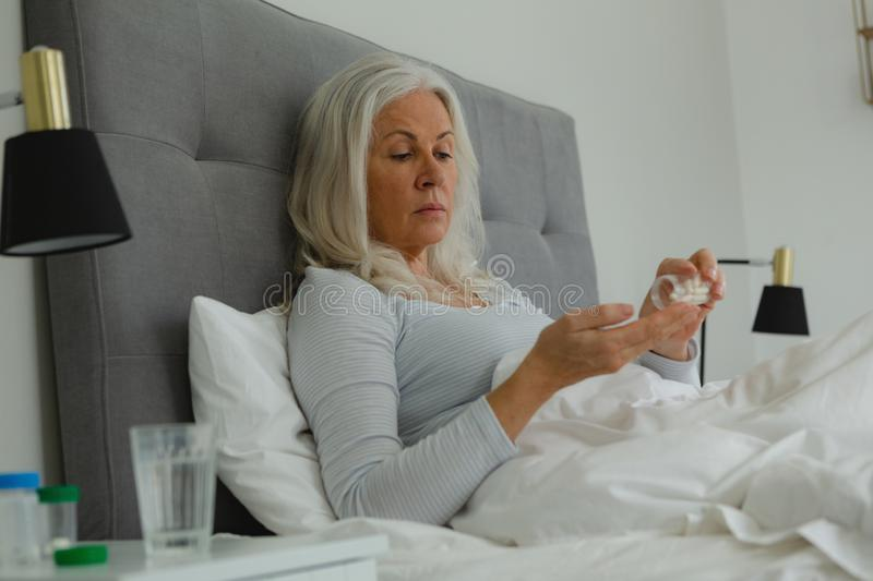 Active senior woman taking medicine in bedroom stock images