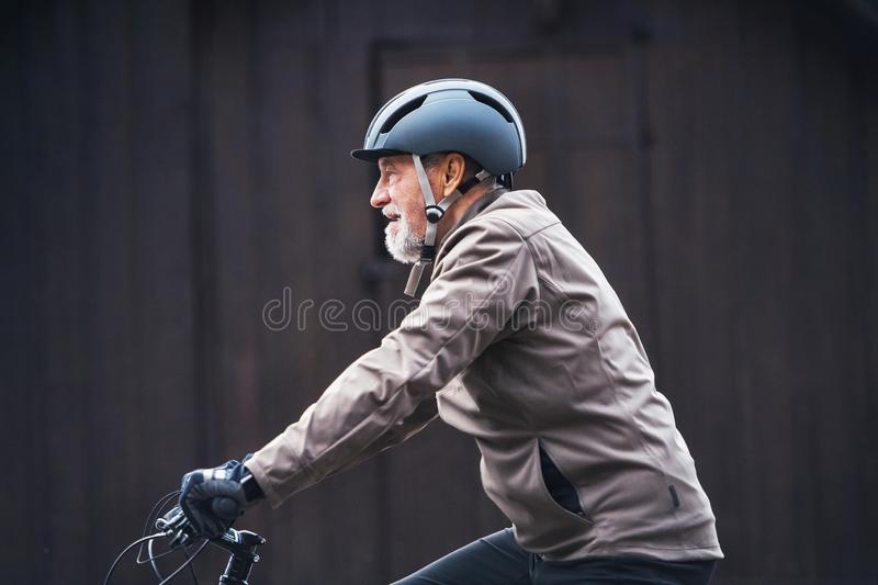 Active senior man with bike helmet cycling outdoors againts dark background. A side view of an active senior man with bike helmet cycling outdoors against dark stock photo