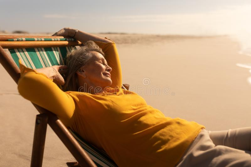 Senior woman sleeping on sun lounger at beach stock images