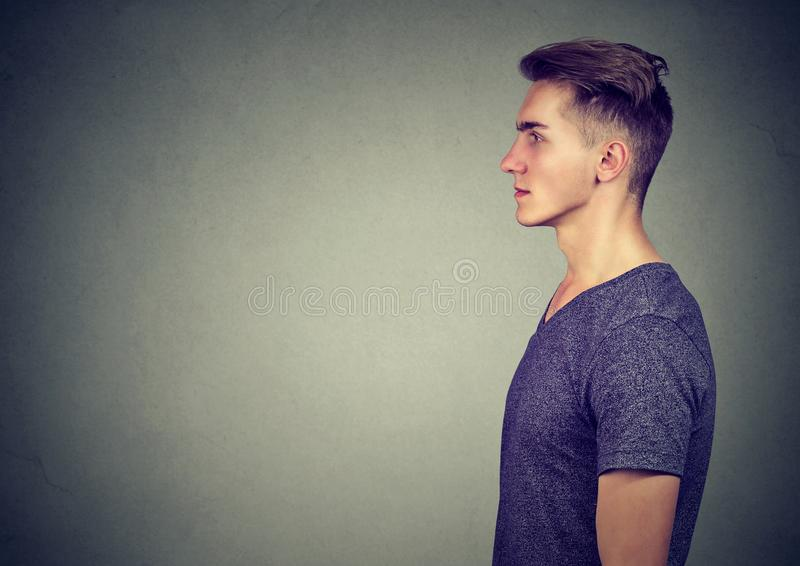 Side view of a modern man in t-shirt looking serious on gray background stock photo