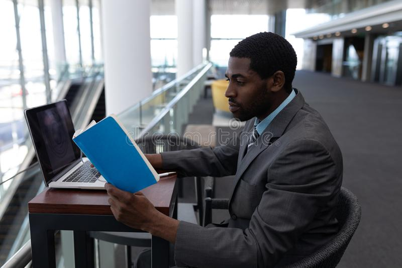 Side view of African-American businessman with laptop sitting at table and reading a book in modern royalty free stock photos