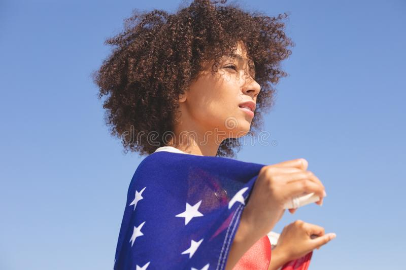 Woman wrapped in american flag looking away on the beach stock photos