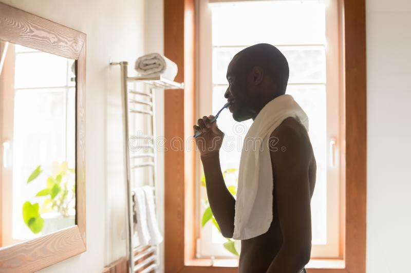 African American man brush teeth after shower in morning royalty free stock photo