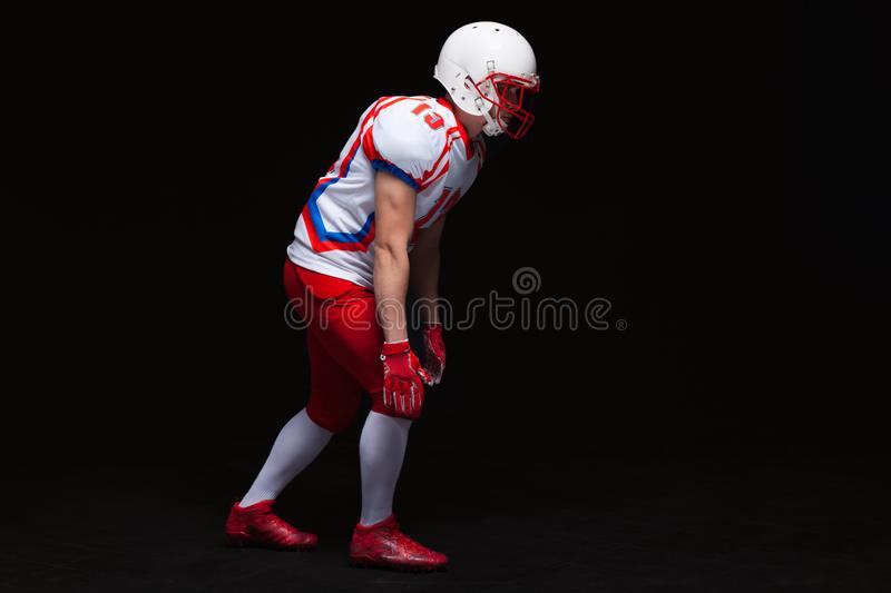 Side view of American football player wearing helmet taking position while playing against black background royalty free stock photography