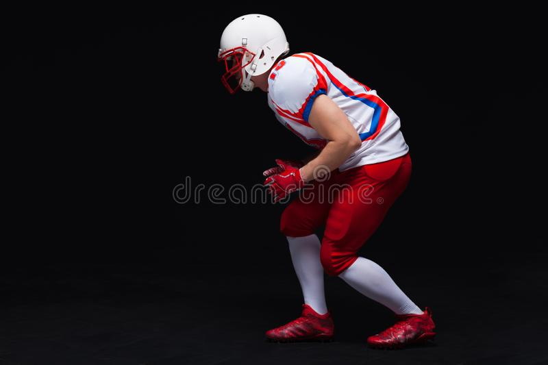 Side view of American football player wearing helmet taking position while playing against black background royalty free stock photo