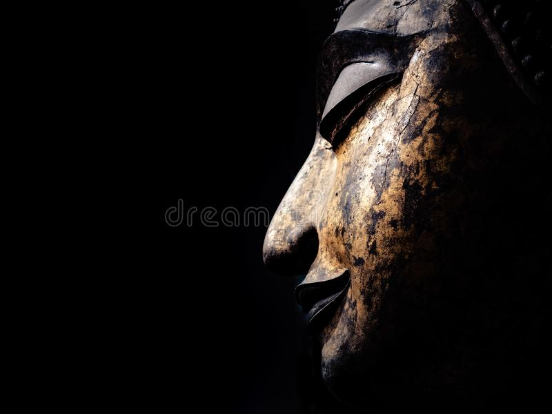 An ancient buddha image's head on black background royalty free stock images
