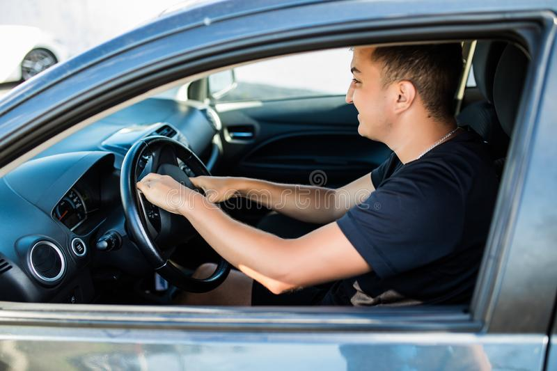 Side view of angry man in suit driving a car and beeps stock image