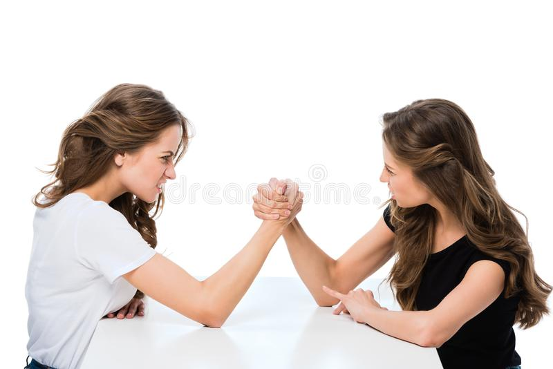 Side view of angry twins armwrestling at table. Isolated on white stock photos