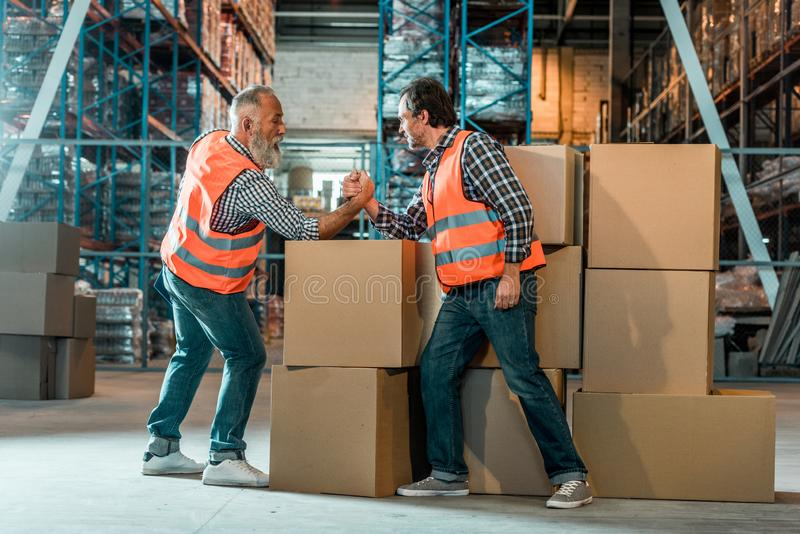 Arm wrestling of warehouse workers. Side view of arm wrestling of warehouse workers on boxes stock photo