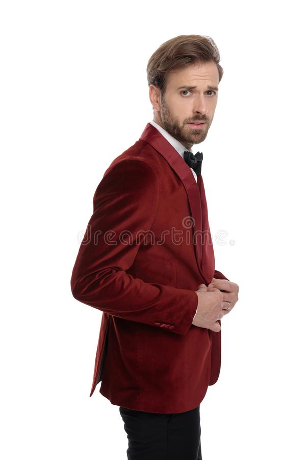 Side view of arrogant young man wearing red velvet tuxedo royalty free stock photo