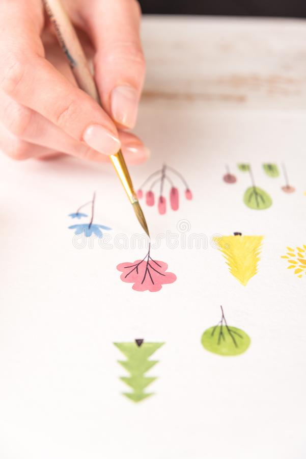 Side view of artist drawing flowers design at workplace. Close up of different colorful flowers nature design painted with brush and watercolors on paper royalty free stock photo