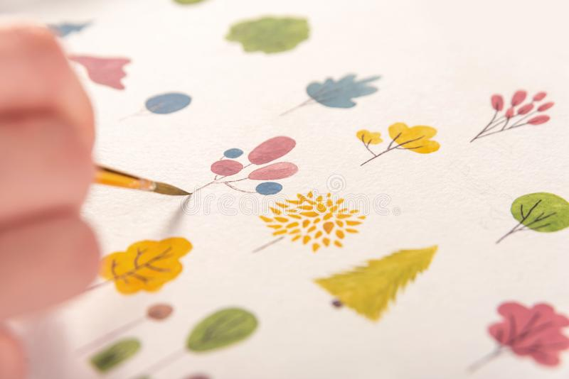 Side view of artist drawing flowers design at workplace. Close up of different colorful flowers nature design painted with brush and watercolors on paper stock photography