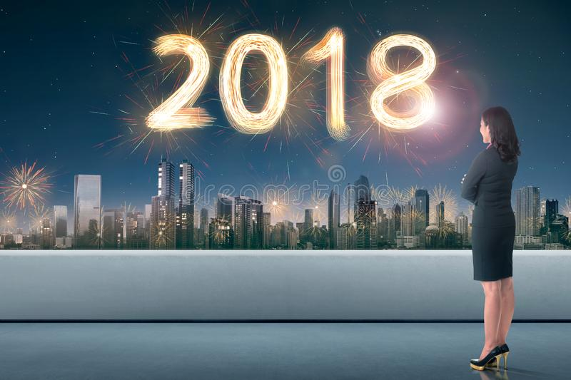 Side view of asian business woman looking cityscape with 2018 firework sparkle. On the sky royalty free stock photo