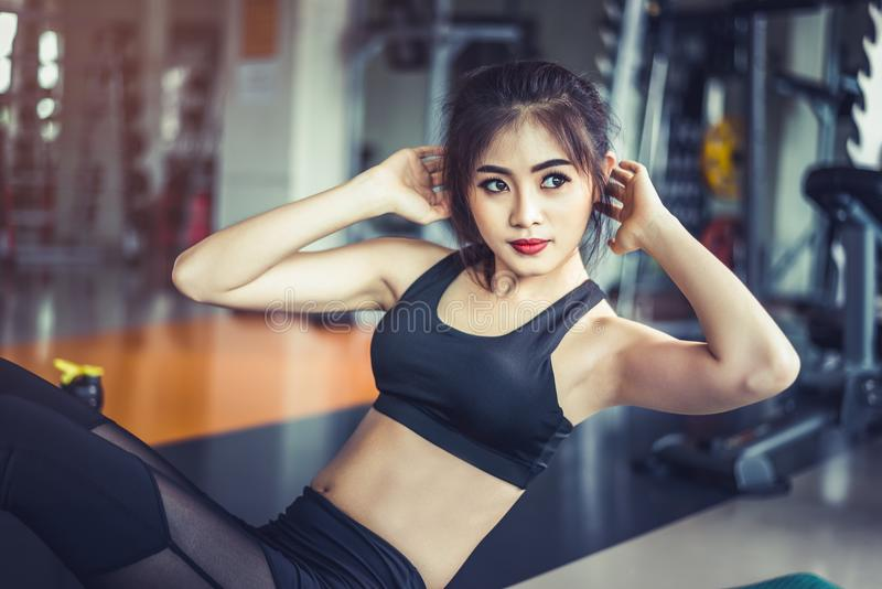 Side view of Asian fitness girl doing crunch twist at fitness gym. Sports and workout concept. Fitness gym and beauty theme. stock image